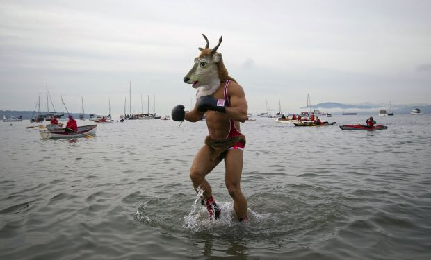 A man wearing a goat mask runs into the English Bay during the annual New Year's Day Polar Bear Swim in Vancouver